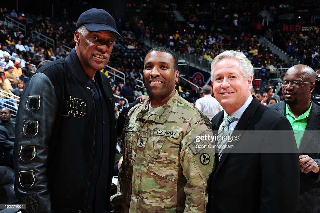 Former NBA legend Julius Erving, a U.S. Army soldier and Bob Williams, President of the Atlanta Hawks pose before the game against of the Los Angeles Lakers on March 13, 2013 at Philips Arena in Atlanta, Georgia.