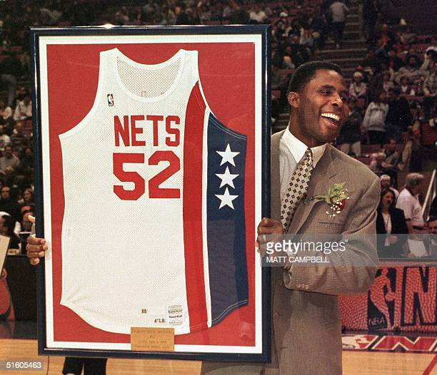 Former NBA player Charles 'Buck' Williams holds his New Jersey Nets jersey which was retired by the Nets during halftime of their game against the...