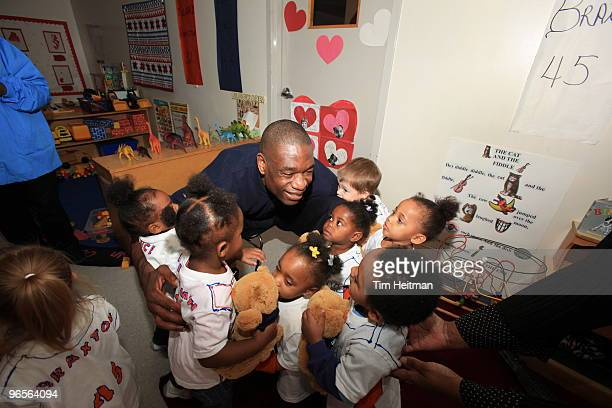 Former NBA player Dikembe Mutombo hugs some kids during the NBA Cares Community Caravan at the Vogel Alcove Childcare Center on February 10 2010 in...