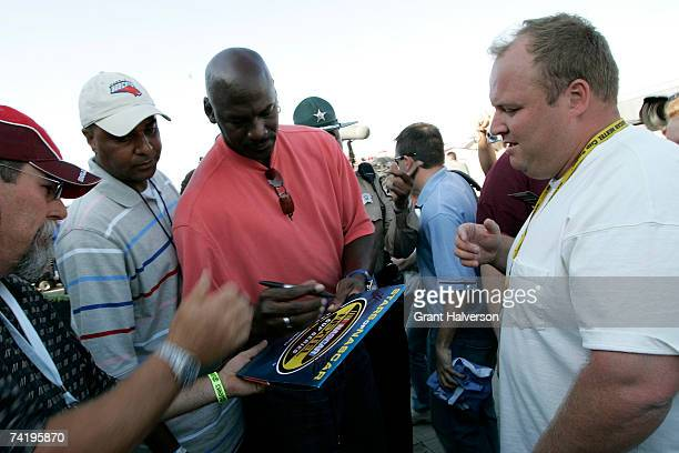 Former NBA player Michael Jordan signs autographs as Fred Whitfield president of the Charlotte Bobcats looks on prior to the NASCAR Nextel Open on...
