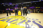Former NBA player Shaquille O'Neal poses for a photograph with Jerry West James Worthy Elgin Baylor Phil Jackson and Jamaal Wilkes during his jersey...