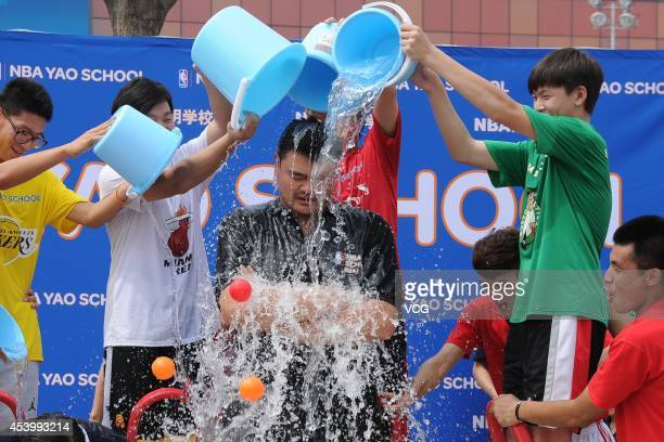 Former NBA player Yao Ming and famous Chinese artist Han Meilin take the ALS Ice Bucket Challenge at Beijing MasterCard Center on August 23 2014 in...
