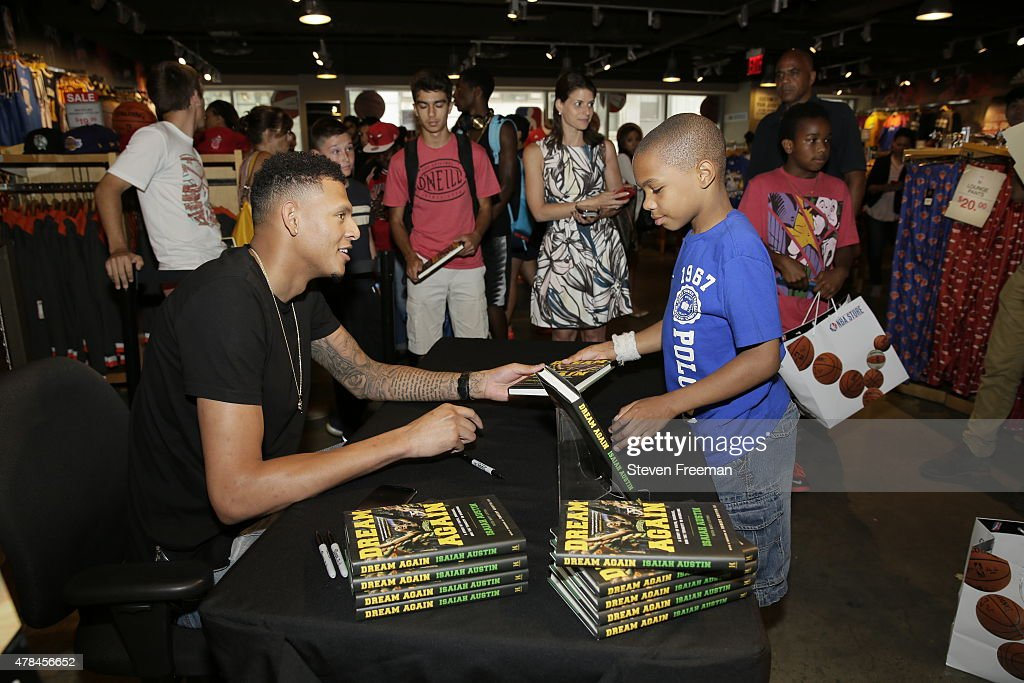 Former NBA prospect Isaiah Austin signs autographs for his book 'Dream Again' at the NBA store during NBA pre draft rookie appearances in New York...