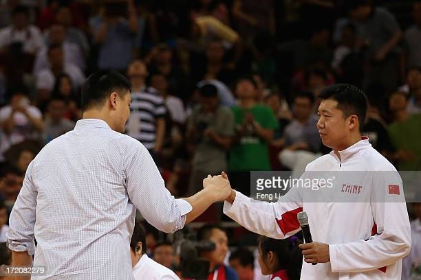 Former NBA star Yao Ming shakes hands with Wang Zhizhi before the 2013 Yao Foundation Charity Game between China team and the NBA Stars team on July...