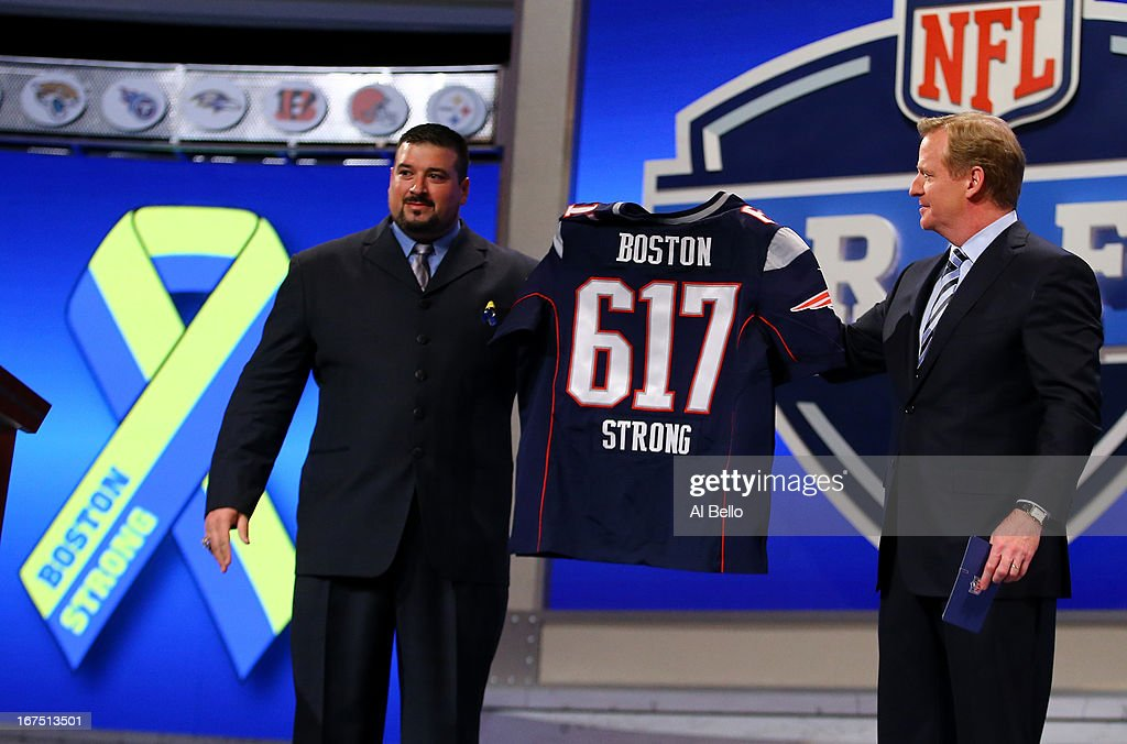 Former New England Patriots player Joe Andruzzi (L) and NFL Commissioner Roger Goodell hold up a New England Patriot jersey with the # 617 on it in honor of the victims and those affected by this years bombing at the Boston Marathon in the first round of the 2013 NFL Draft at Radio City Music Hall on April 25, 2013 in New York City.