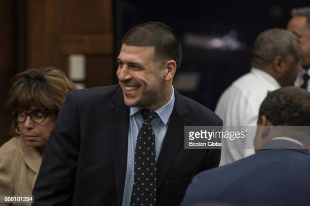 Former New England Patriots tight end Aaron Hernandez smiles at the sight of his fiancées Shayanna Jenkins from the defense table during jury...