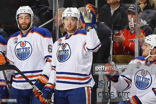 Former New Jersey Devil defenseman Adam Larsson of the Edmonton Oilers waves to the crowd after a video tribute during the game against the at...