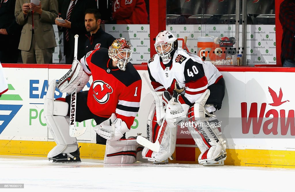 Former New Jersey Devil Scott Wedgewood #40 of the Arizona Coyotes talks with Keith Kinkaid #1 of the New Jersey Devils during pregame warmups prior to the start of the game at Prudential Center on October 28, 2017 in Newark, New Jersey.