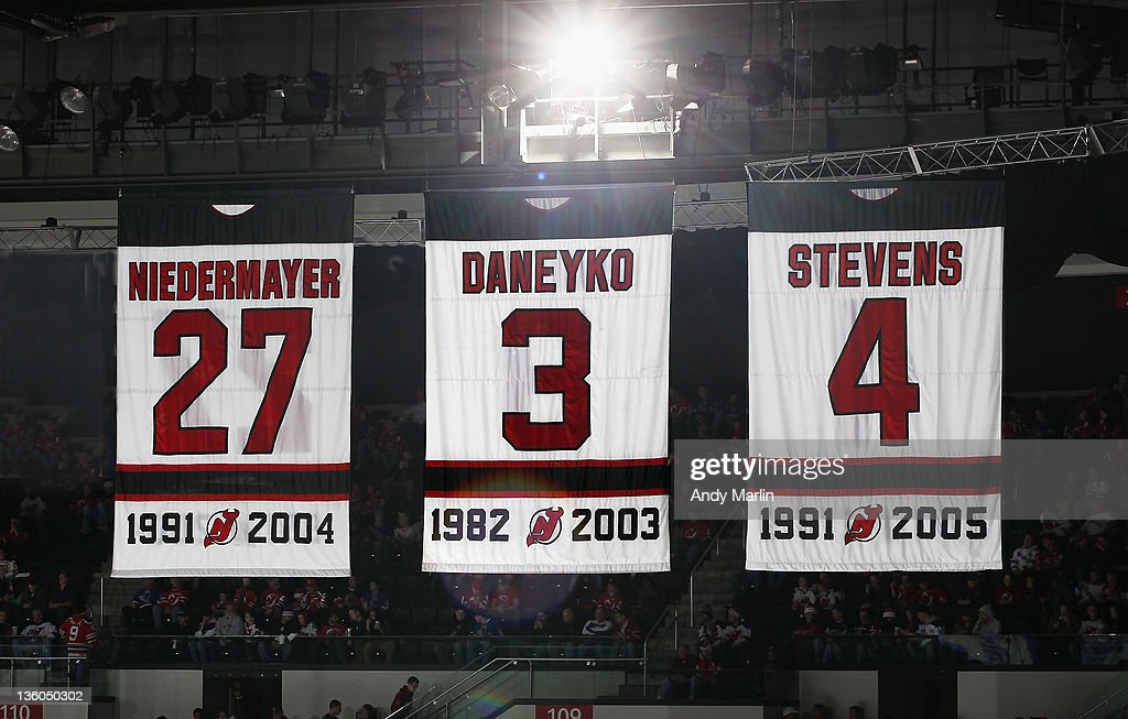 Former New Jersey Devils Scott Niedermayer's retired jersey # 27 hangs from the rafters next to Ken Daneyko's #3 and Scott Stevens' #4 during the game against the New York Rangers at the Prudential Center on December 20, 2011 in Newark, New Jersey.