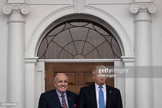 Former New York City mayor Rudy Giuliani stands with presidentelect Donald Trump before their meeting at Trump International Golf Club November 20...