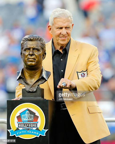 Former New York Giants head coach Bill Parcells poses with his Pro Football Hall of Fame bust and ring as he is honored at halftime of a game between...