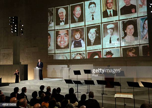 Former New York Gov George Pataki speaks as photos of 9/11 victims are projected during the dedication ceremony in Foundation Hall at the National...