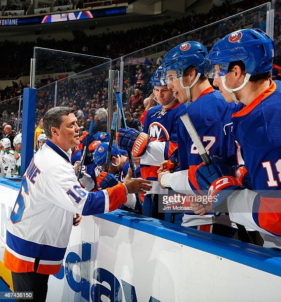 Former New York Islander and a member of the NHL Hall of Fame Pat LaFontaine shakes hands with present Islanders players after being honored prior to...
