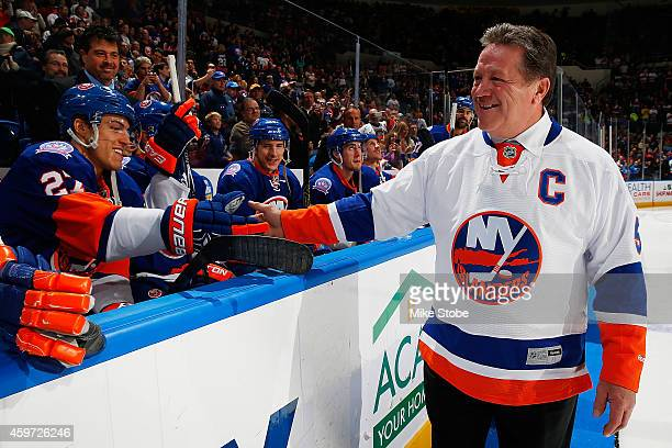 Former New York Islanders captain Denis Potvin greets Anders Lee of the New York Islanders before dropping the ceremonial first puck before the game...