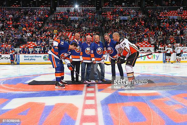 Former New York Islanders players Bobby Nystrom Billy Smith Bryan Trottier and Eric Cairns pose for a photo during a ceremonial puck drop with John...