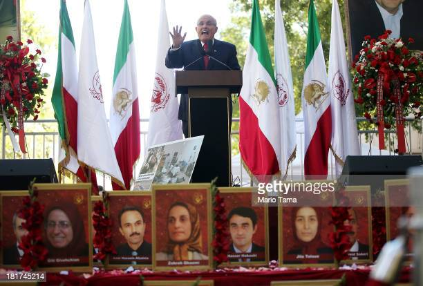 Former New York Mayor Rudolph Giuliani speaks in front of portraits of deceased members of the Iranian dissident group MujahedeeneKhalq whose members...