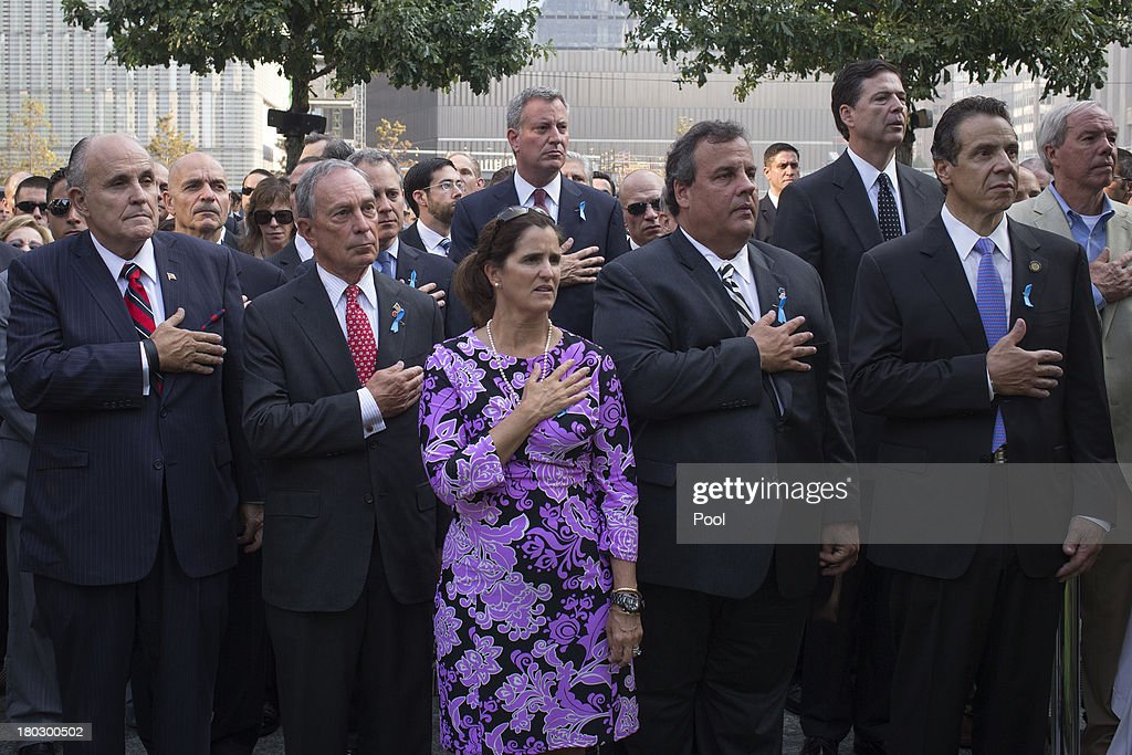 Former New York Mayor Rudy Giuliani (L-R), New York Mayor Michael Bloomberg, New Jersey Governor Chris Christie with wife Mary Pat Christie and New York State Governor Andrew Cuomo take part in the national anthem while attending the 9/11 Memorial ceremonies marking the 12th anniversary of the 9/11 attacks on the World Trade Center on September 11, 2013 in New York City. The nation is commemorating the anniversary of the 2001 attacks which resulted in the deaths of nearly 3,000 people after two hijacked planes crashed into the World Trade Center, one into the Pentagon in Arlington, Virginia and one crash landed in Shanksville, Pennsylvania. Following the attacks in New York, the former location of the Twin Towers has been turned into the National September 11 Memorial & Museum.