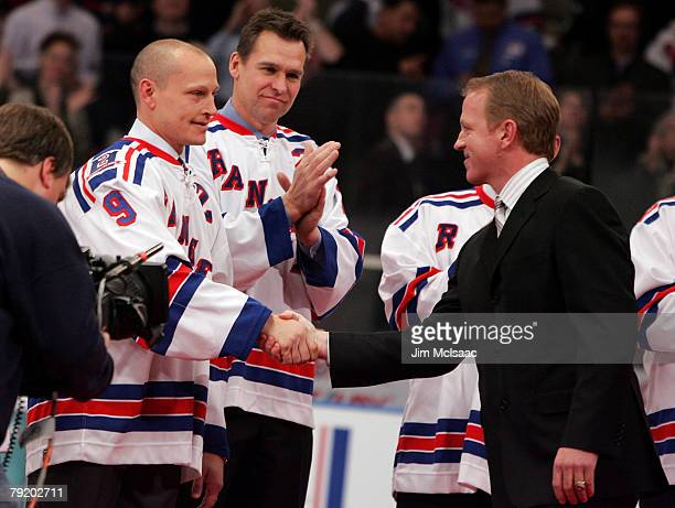 Former New York Ranger Brian Leetch shakes hands with former teammate Adam Graves during his jersey retirment ceremony before the game against the...
