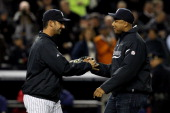 Former New York Yankee Bernie Williams greets Jorge Posada after throwing out the first pitch prior to Game Four of the ALCS during the 2010 MLB...