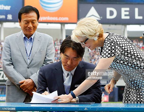 Former New York Yankee Hideki Matsui signs his reitement papers with Yankees assistant general manager Jean Afterman as general his father Masao...