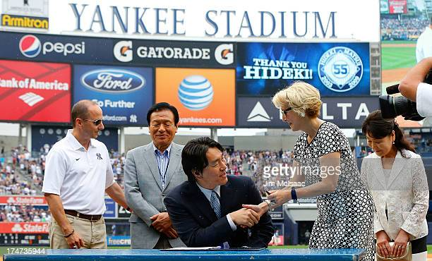 Former New York Yankee Hideki Matsui signs his reitement papers with Yankees assistant general manager Jean Afterman as general manager Brian Cashman...