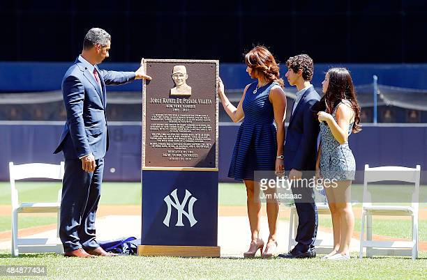 Former New York Yankee Jorge Posada looks at his Monument Park plaque with his wife Laura son Jorge and daughter Paulina during a ceremony before the...