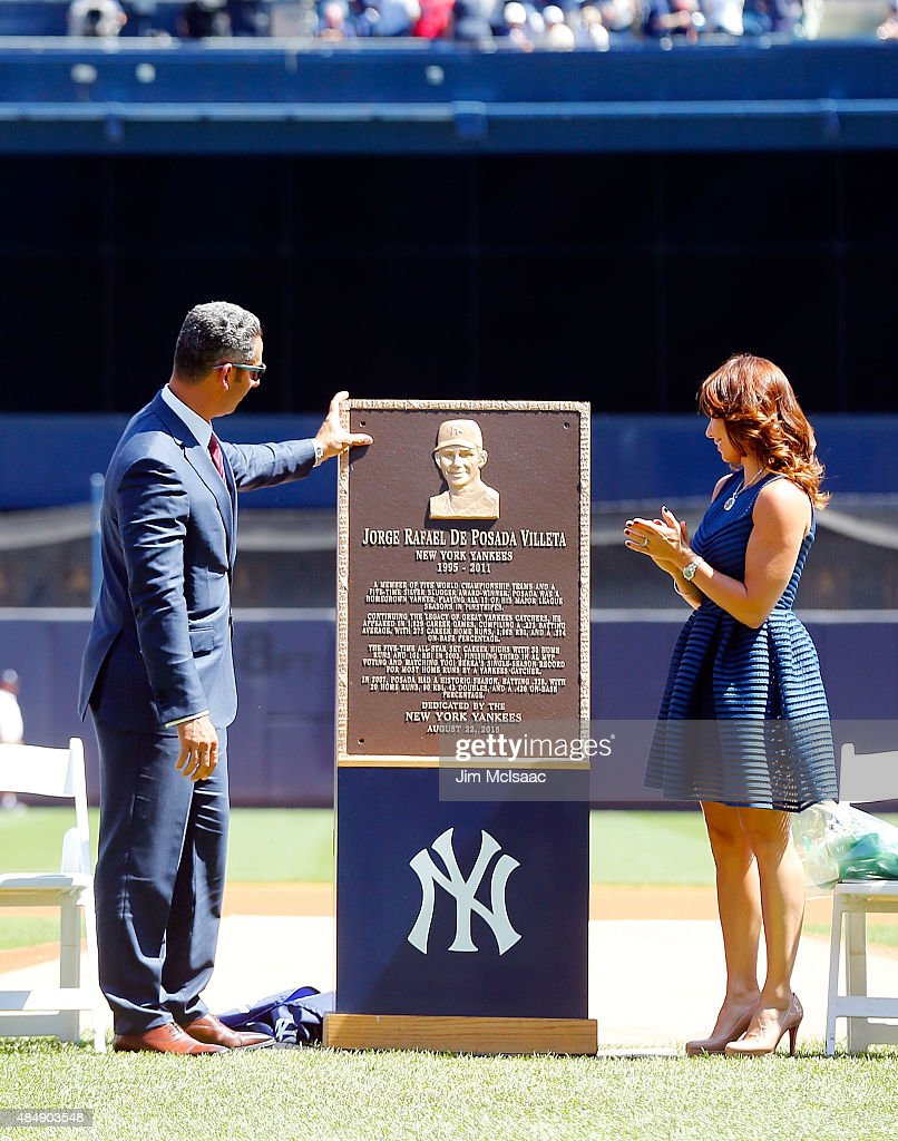 Former New York Yankee Jorge Posada looks at his Monument Park plaque with his wife Laura during a ceremony before the Yankees play against the Cleveland Indians at Yankee Stadium on August 22, 2015 in the Bronx borough of New York City.