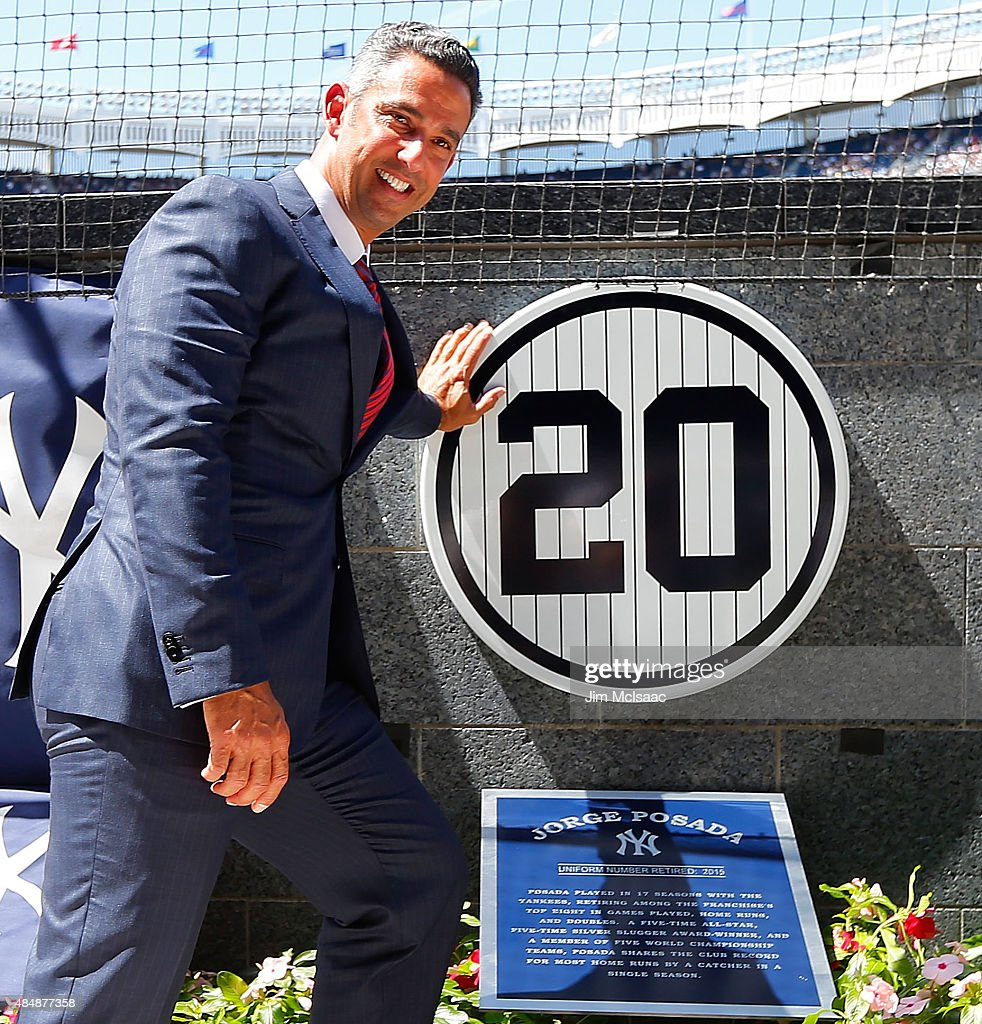 Former New York Yankee Jorge Posada poses for a photograph with his retired number plaque in Monument Park during a ceremony before the Yankees play against the Cleveland Indians at Yankee Stadium on August 22, 2015 in the Bronx borough of New York City.