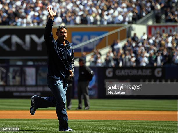 Former New York Yankees catcher Jorge Posada waves to the crowd after throwing out the ceremonial first pitch during the Yankees' home opener against...