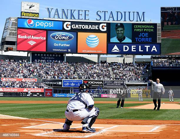 Former New York Yankees manager Joe Torre throws out the ceremonial first pitch to Brian McCann of the New York Yankees before the Opening Day game...