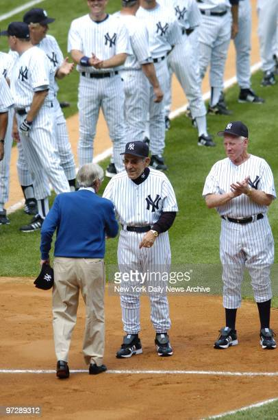 Former New York Yankees' shortstop Phil Rizzuto shakes hands with former Yanks' catcher and manager Yogi Berra as former Yankees' pitcher Whitey Ford...