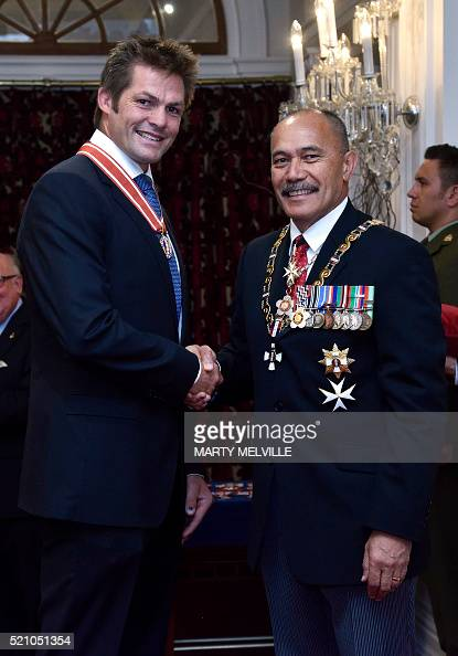 Former New Zealand All Blacks rugby union captain Richie McCaw shakes hands with Governor General Lieutenant General Jerry Mateparae upon receiving...