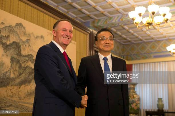 Former New Zealand prime minister John Key shakes hands with Chinese Premier Li Keqiang at the Zhongnanhai Leadership compound in Beijing on July 20...