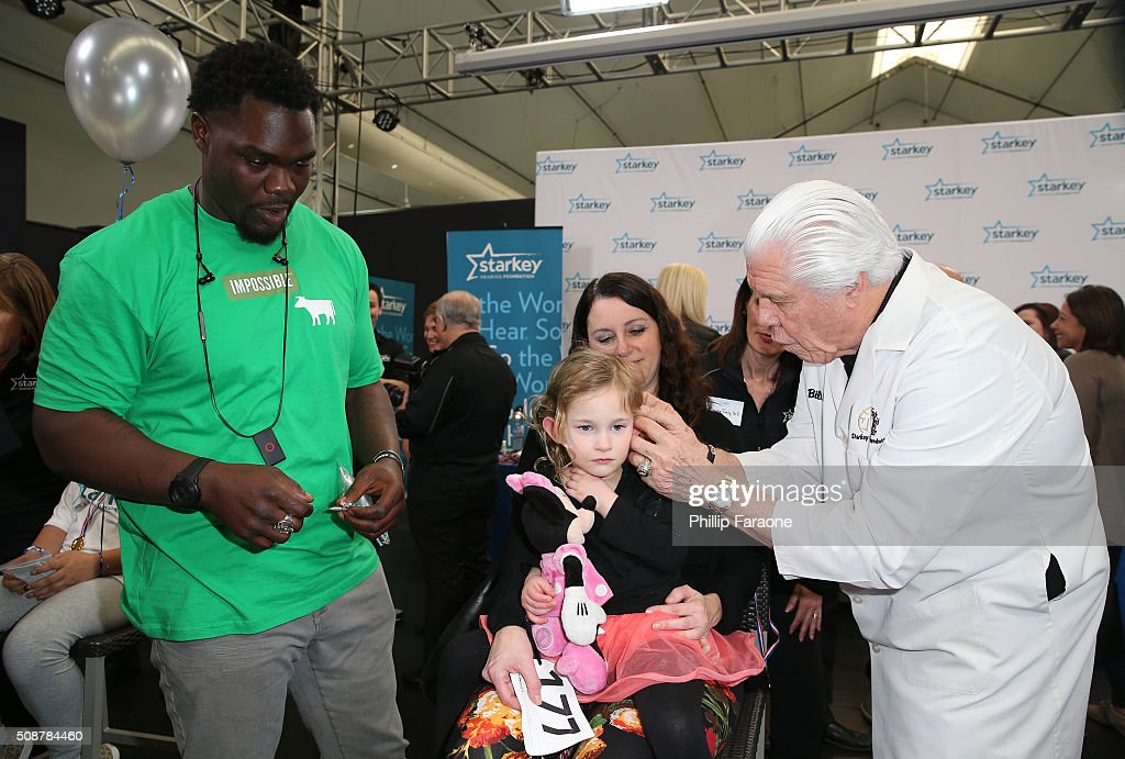 Former NFL player <a gi-track='captionPersonalityLinkClicked' href=/galleries/search?phrase=Tommie+Harris&family=editorial&specificpeople=182574 ng-click='$event.stopPropagation()'>Tommie Harris</a> helps Dr. Bill Austin with the fitting of a hearing aid for a patient at the Starkey Hearing Foundation hearing mission during Super Bowl weekend 2016 at San Francisco State University on February 6, 2016 in San Francisco, California.