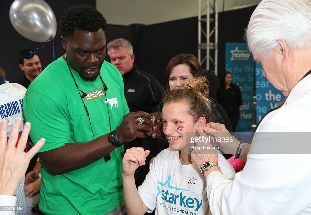 Former NFL player <a gi-track='captionPersonalityLinkClicked' href=/galleries/search?phrase=Tommie+Harris&family=editorial&specificpeople=182574 ng-click='$event.stopPropagation()'>Tommie Harris</a> helps with the fitting of a hearing aid for patient Chloe at the Starkey Hearing Foundation hearing mission during Super Bowl weekend 2016 at San Francisco State University on February 6, 2016 in San Francisco, California.