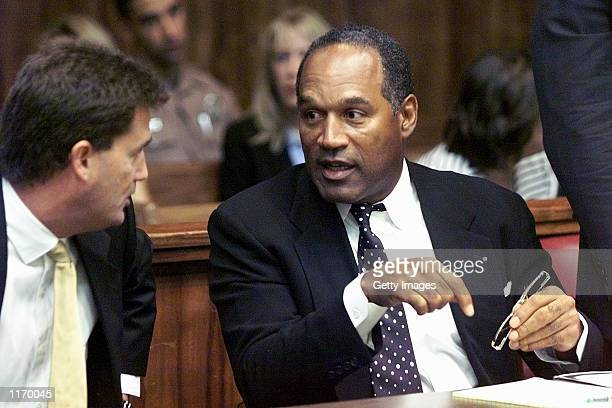 Former NFL star OJ Simpson talks with one of his defense attorneys on the first day of jury selection October 9 2001 at a Dade County courtroom in...