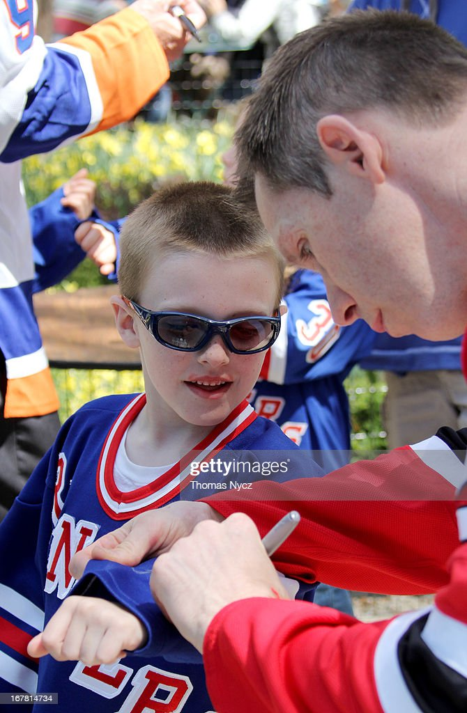 Former NHL player <a gi-track='captionPersonalityLinkClicked' href=/galleries/search?phrase=Grant+Marshall&family=editorial&specificpeople=201701 ng-click='$event.stopPropagation()'>Grant Marshall</a> poses for signs a jersey for a young fan during a 2013 Stanley Cup Playoffs kickoff event at Madison Square Park on April 30, 2013 in New York City. The NHL, NBC Sports and Crumbs Bake Shop hosted the event to celebrate the start of the 2013 Stanley Cup Playoffs.