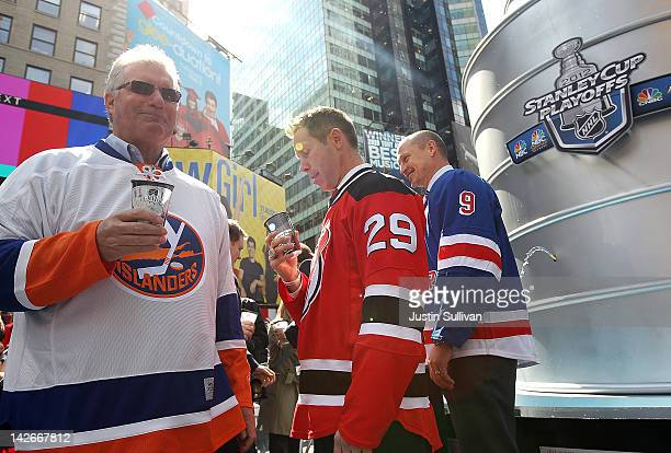 Former NHL players Clark Gillies Grant Marshall and Adam Graves stand next to a 21 foot replica of the Stanley Cup trophy in Times Square on April 11...