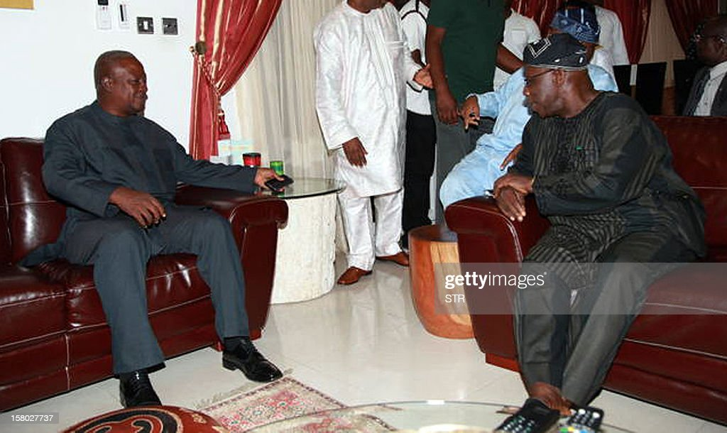 Former Nigerian President and head of the Economic Community of West African States (ECOWAS) monitoring team for Ghana's 2012 election Olusegun Obasanjo (R) speaks with newly elected Ghanaian President John Dramani Mahama (C), candidate of the ruling National Democratic Congress party, who replaced the late President John Atta-Mills after his death in July, at his residence in Accra on December 9, 2012. Obasanjo paid Mahama a visit ahead of the final results announcement for Ghana's just concluded presidential and parliamentary elections that were acclaimed by the ECOWAS observers as 'peaceful and transparent.' Mahama held a slight edge over his main rival as vote counting wrapped up on December 9 after high-stakes presidential polls in the emerging west African country, local media said. AFP PHOTO / STRINGER