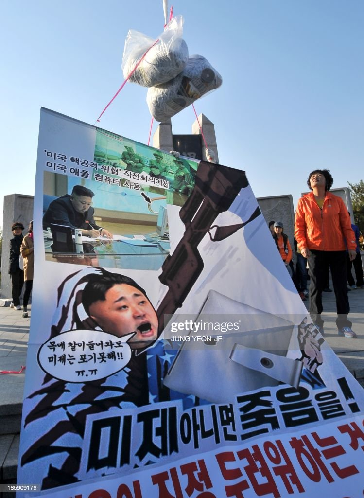 Former North Korean defectors display a banner showing a portrait of North Korean leader Kim Jong-Un as they release anti-Pyongyang leaflets at Imjingak peace park in Paju near the Demilitarized Zone (DMZ) dividing the two Koreas on October 26, 2013. Activists launched balloons across the border carrying leaflets that criticise North Korea's ruling Kim family and demanding informations of US soldiers kept in North Korea during the Korean War.