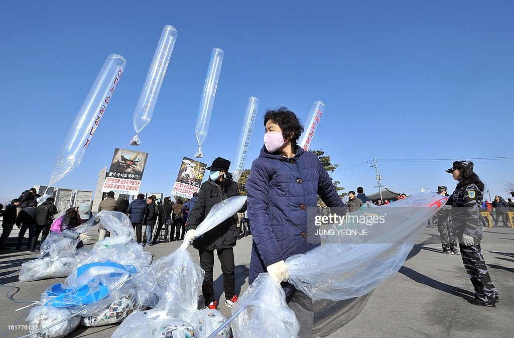 Former North Korean defectors (L) living in South Korea float giant balloons carrying anti-Pyongyang leaflets at Imjingak park near the inter-Korean border in Paju on February 16, 2013. Activists launched balloons across the border carrying leaflets that criticise North Korea's ruling Kim family on the birth anniversary of late leader Kim Jong-Il, amid high tension over its long-range rocket launch and nuclear test.