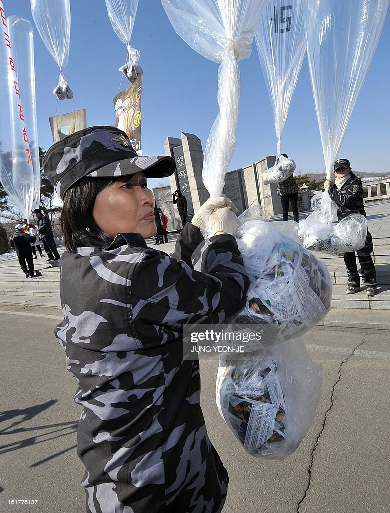 Former North Korean defectors living in South Korea prepare to float giant balloons carrying anti-Pyongyang leaflets at Imjingak park near the inter-Korean border in Paju on February 16, 2013. Activists launched balloons across the border carrying leaflets that criticise North Korea's ruling Kim family on the birth anniversary of late leader Kim Jong-Il, amid high tension over its long-range rocket launch and nuclear test.