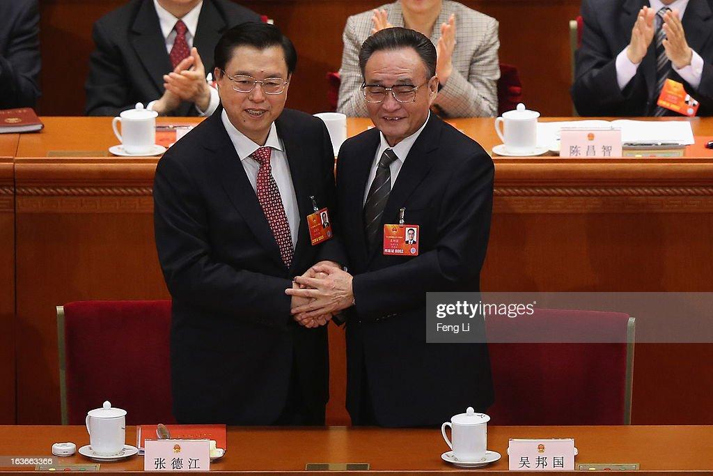 Former NPC Chairman Wu Bangguo shakes hands with newlyelected NPC Chairman Zhang Dejiang during the fourth plenary meeting of the National People's...