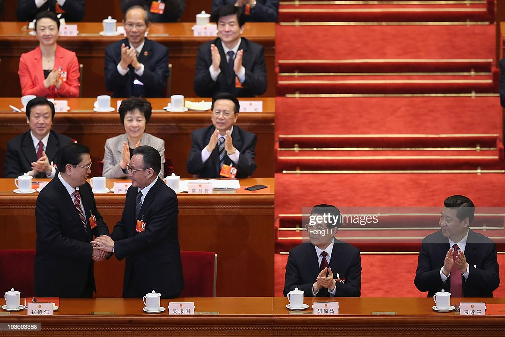 Former NPC Chairman <a gi-track='captionPersonalityLinkClicked' href=/galleries/search?phrase=Wu+Bangguo&family=editorial&specificpeople=604934 ng-click='$event.stopPropagation()'>Wu Bangguo</a> (2nd L) shakes hands with newly-elected NPC Chairman Zhang Dejiang (L) as China's newly-elected President <a gi-track='captionPersonalityLinkClicked' href=/galleries/search?phrase=Xi+Jinping&family=editorial&specificpeople=2598986 ng-click='$event.stopPropagation()'>Xi Jinping</a> (R) and former President Hu Jintao (2nd R) looks on during the fourth plenary meeting of the National People's Congress (NPC) at the Great Hall of the People on March 14, 2013 in Beijing, China. <a gi-track='captionPersonalityLinkClicked' href=/galleries/search?phrase=Xi+Jinping&family=editorial&specificpeople=2598986 ng-click='$event.stopPropagation()'>Xi Jinping</a>, general secretary of the Communist Party of China Central Committee, was elected President of the People's Republic of China and Chairman of the Central Military Commission on Thursday.