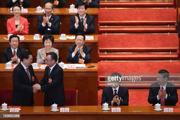 Former NPC Chairman Wu Bangguo shakes hands with newlyelected NPC Chairman Zhang Dejiang as China's newlyelected President Xi Jinping and former...