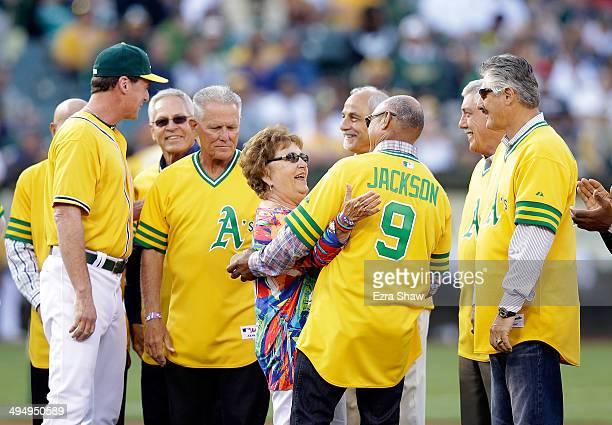 Former Oakland Athletics Reggie Jackson hugs Helen Hunter the widow of former Oakland Athletics pitcher Jim 'Catfish' Hunter during a ceremony...