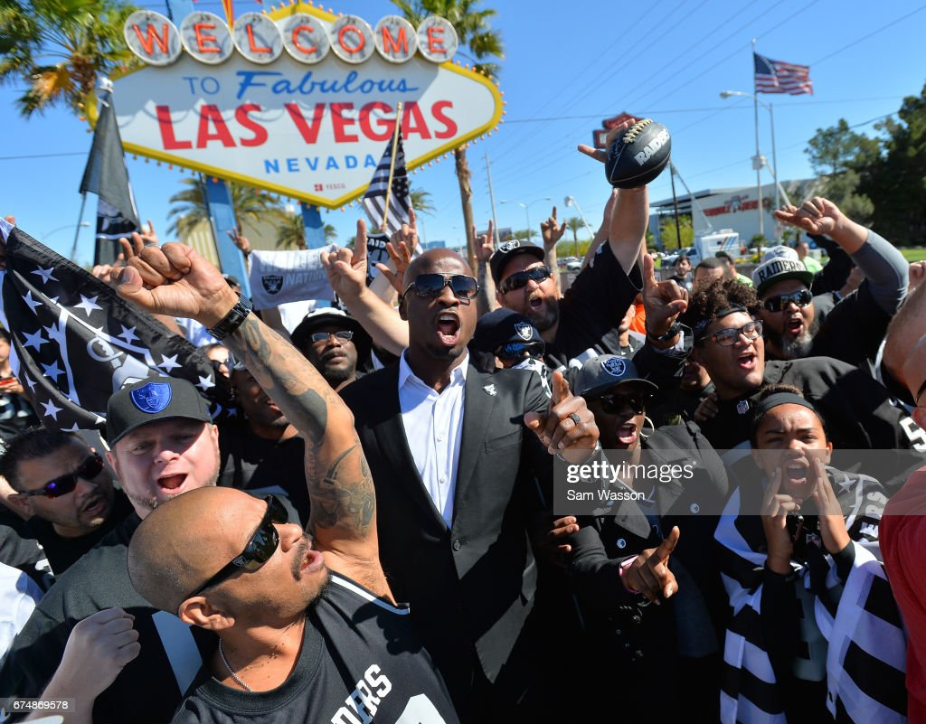 Former Oakland Raiders player Akbar Gbajabiamila (center) leads Oakland Raiders fans in a cheer during the team's 2017 NFL Draft event at the Welcome to Fabulous Las Vegas sign on April 29, 2017 in Las Vegas, Nevada. National Football League owners voted in March to approve the team's application to relocate to Las Vegas. The Raiders are expected to begin play no later than 2020 in a planned 65,000-seat domed stadium to be built in Las Vegas at a cost of about USD 1.9 billion.