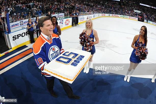 Former Oiler Craig Simpson presents a birthday cake for Oilers' legendary dressing room attendant Joey Moss' 50th Birthday following the first period...