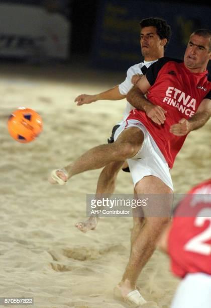 Former Old Trafford favourite Eric Cantona kicks the ball as Emirati defender Ibrahim Abdul Razzaq runs behind him during their Dubai ProBeach Soccer...