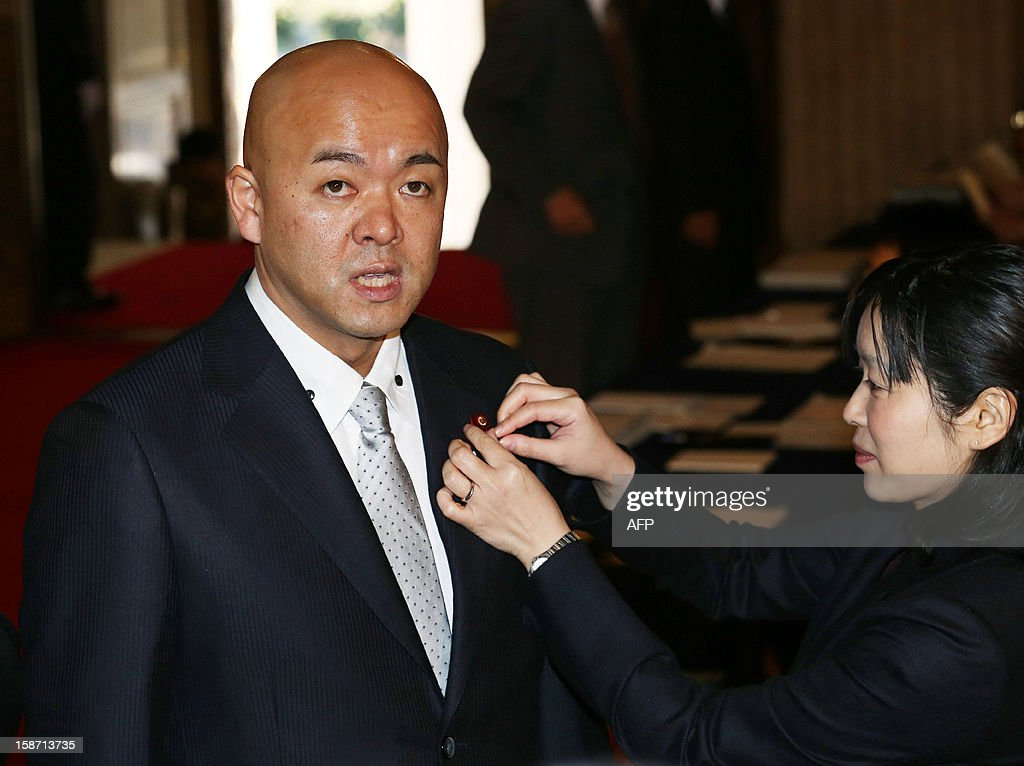 Former Olympic speed skating medalist and a member of the Liberal democratic Party (LDP) Manabu Horii (L) smiles as he receives a Diet member's badge from an official at the National Diet in Tokyo on December 26, 2012. Japan's conservative leader Shinzo Abe is to be named as the country's new prime minister on December 26, after he swept to power on a hawkish platform of getting tough on diplomacy while fixing the economy. AFP PHOTO / JIJI PRESS JAPAN OUT